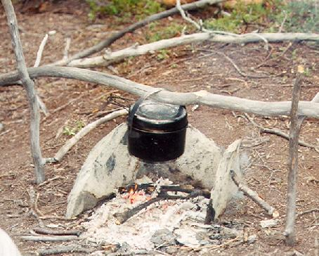 Pot with handle hanging over a campfire